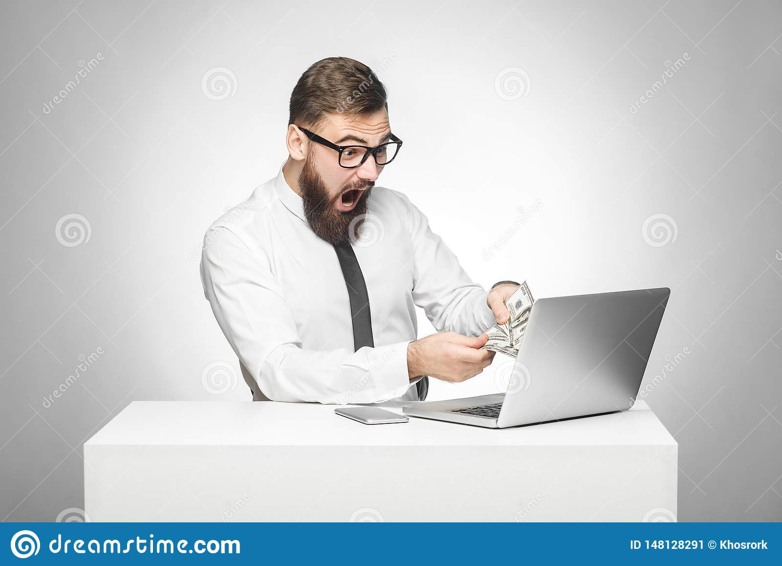 Het portret van emotionele geschokte jonge zakenman in wit overhemd en de avondkleding zitten in het contante geld van de bureauh