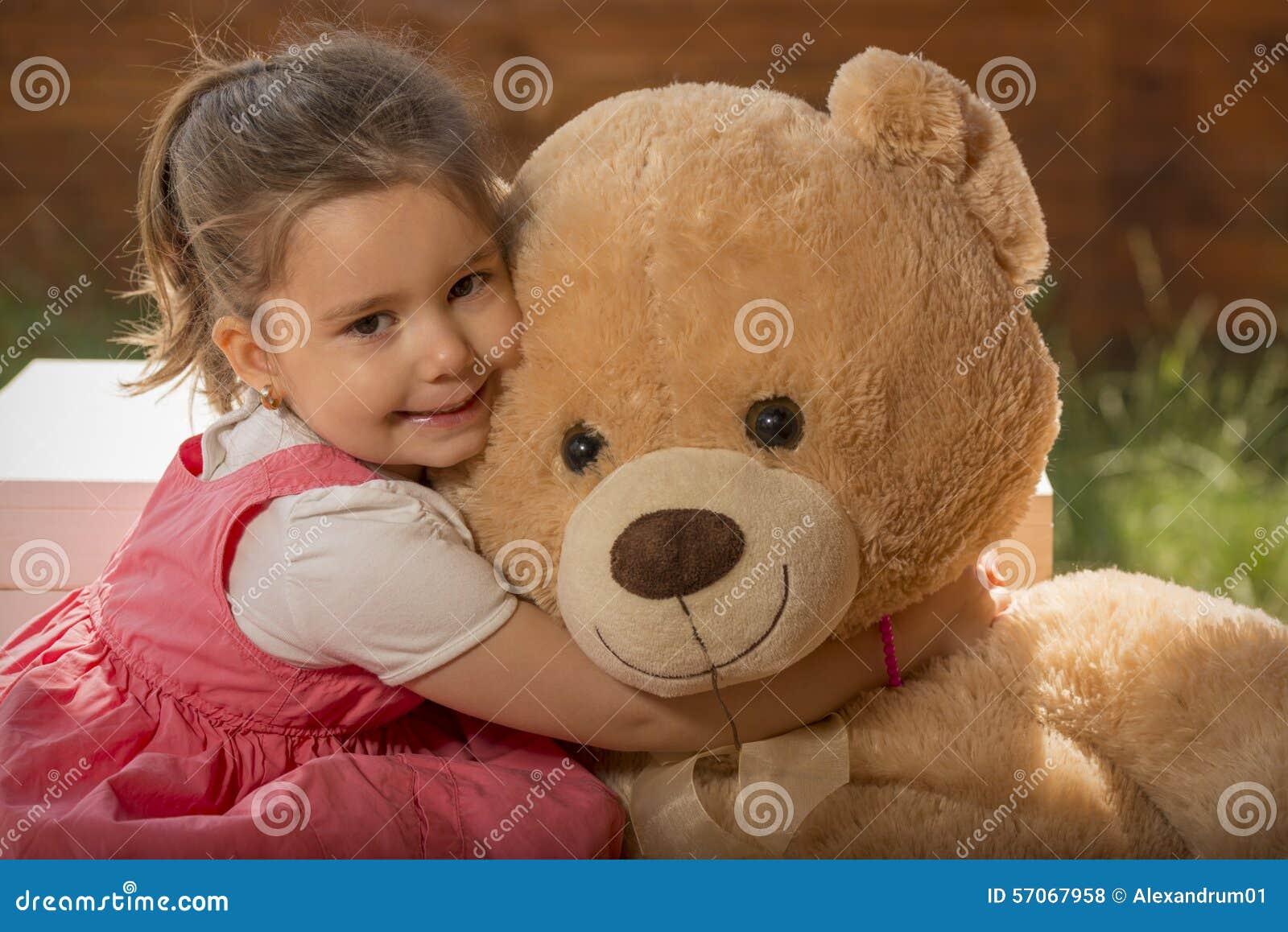 Het portret van expressief meisje die haar stuk speelgoed koesteren draagt