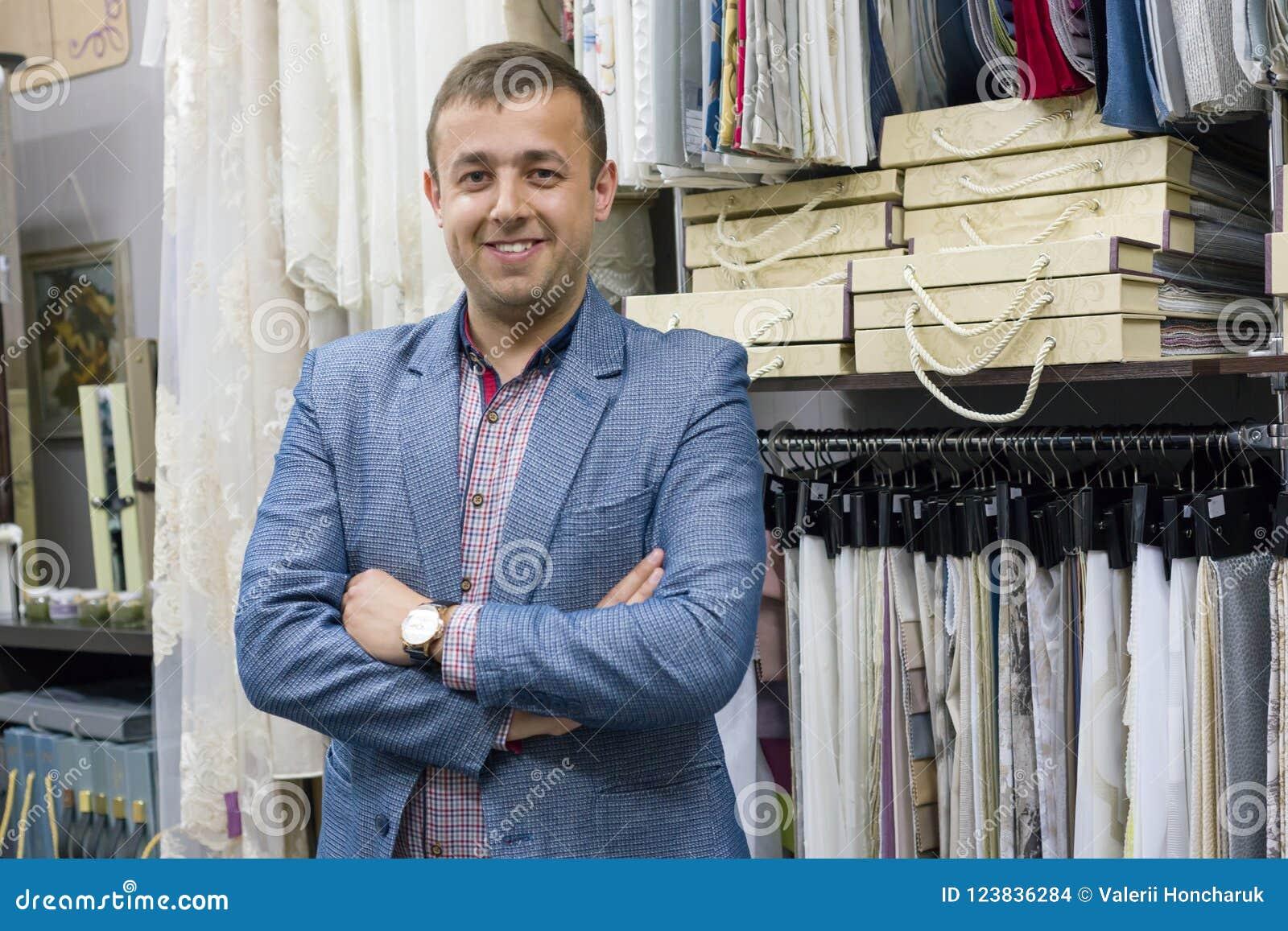Het portret van gelukkige zakenmaneigenaar met gekruiste wapens in binnenlandse stoffen slaat, achtergrondstoffensteekproeven op