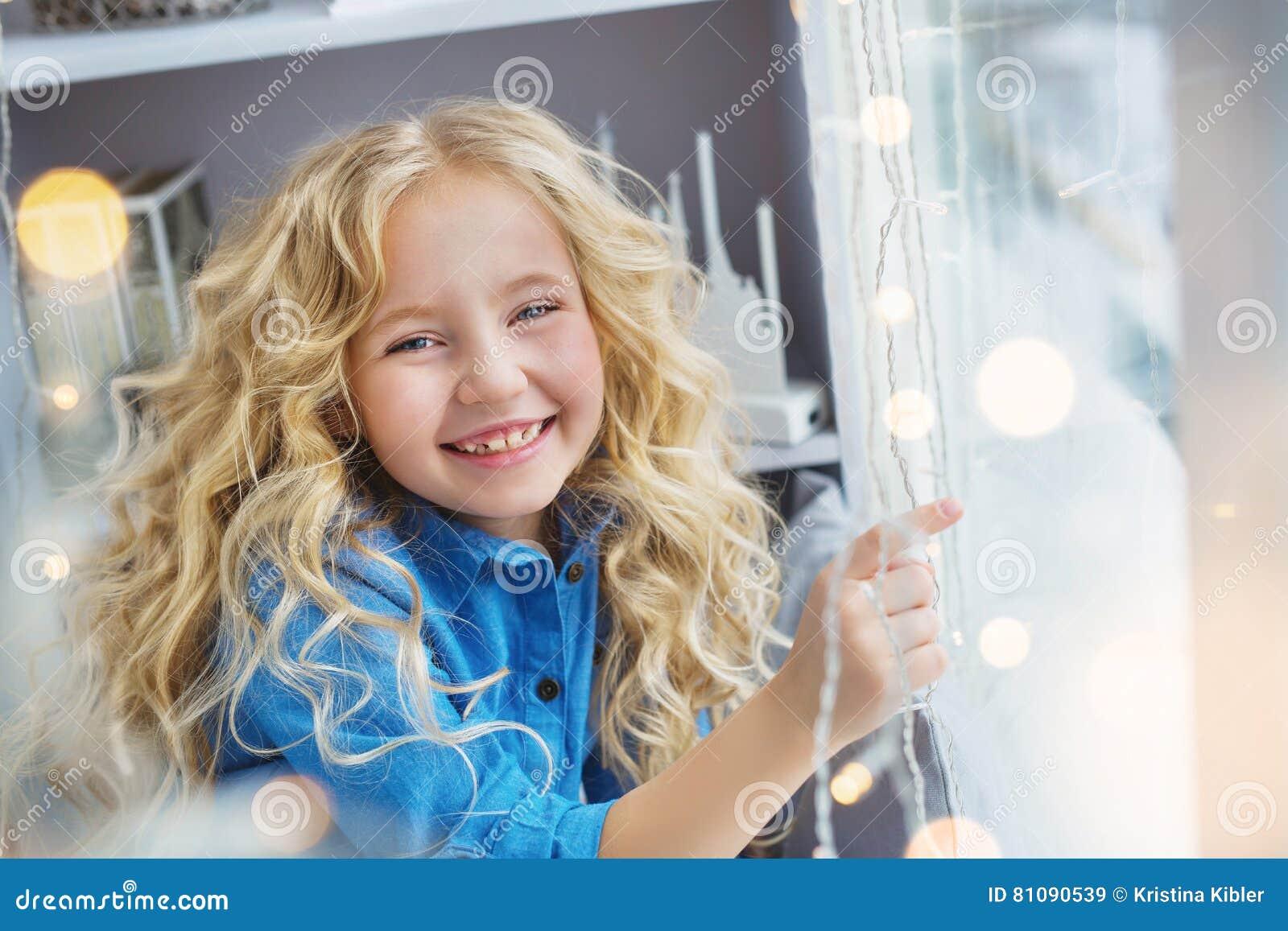 Het portret van glimlachend mooi meisje zit op de vensterbank