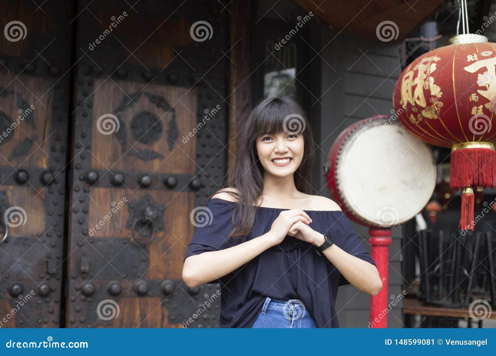 Het portret van glimlachende jonge Aziatische vrouw geniet van in de stad van China