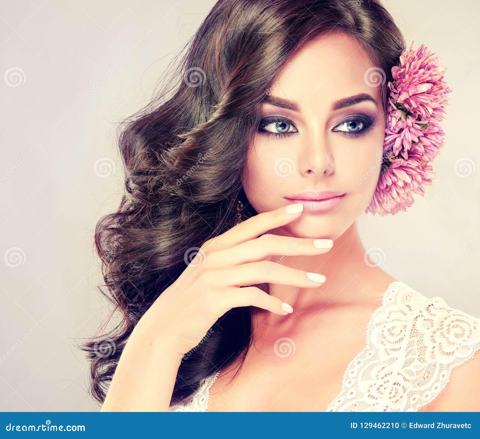 Het portret van jong krullend haired brunette met levendige oostelijke stijl maakt omhoog Elegante krullende kapsels