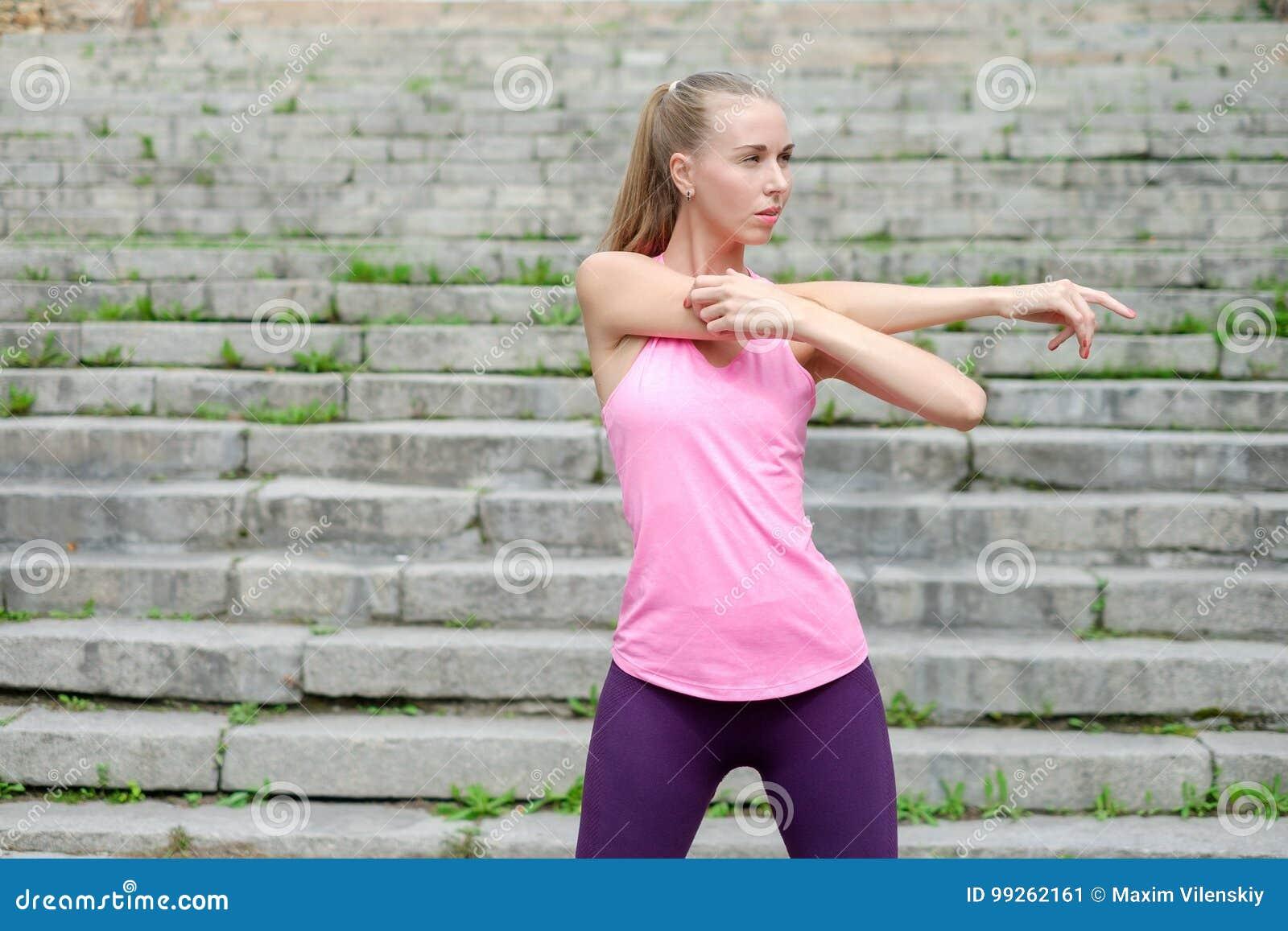 Het portret van jonge sportieve vrouw in sportkleding doet uitrekkende oefeningen openlucht