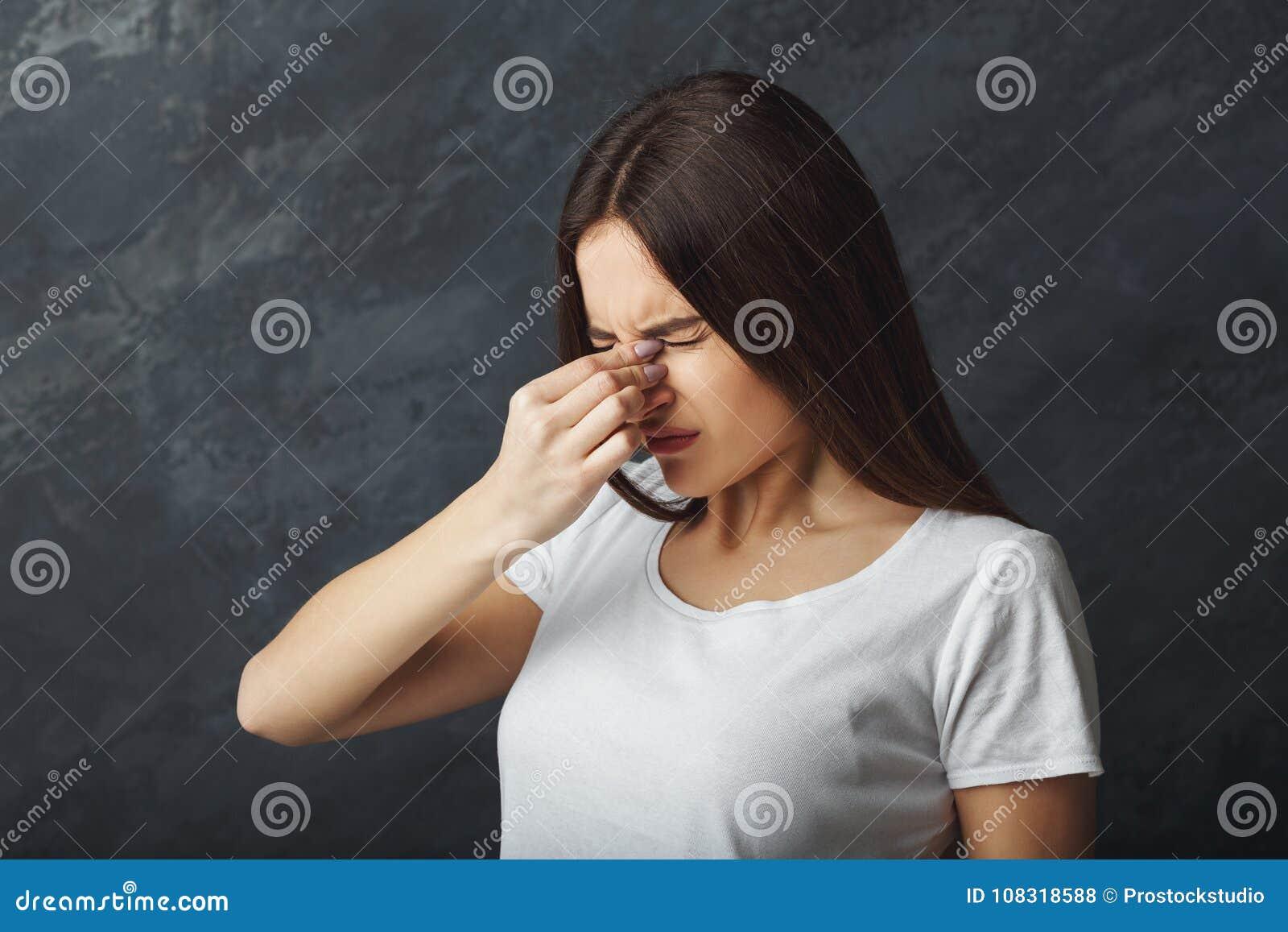 Het portret van jonge vrouw heeft hoofdpijn