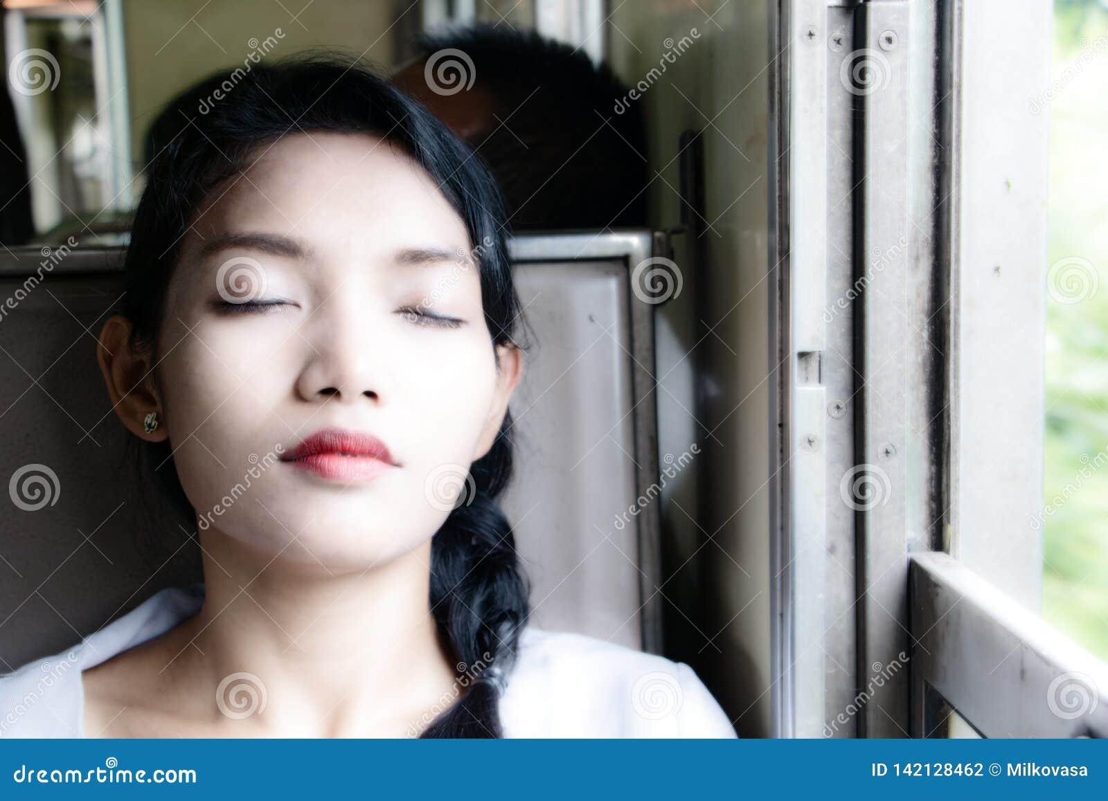 Het portret van jonge vrouwenslaap in de trein