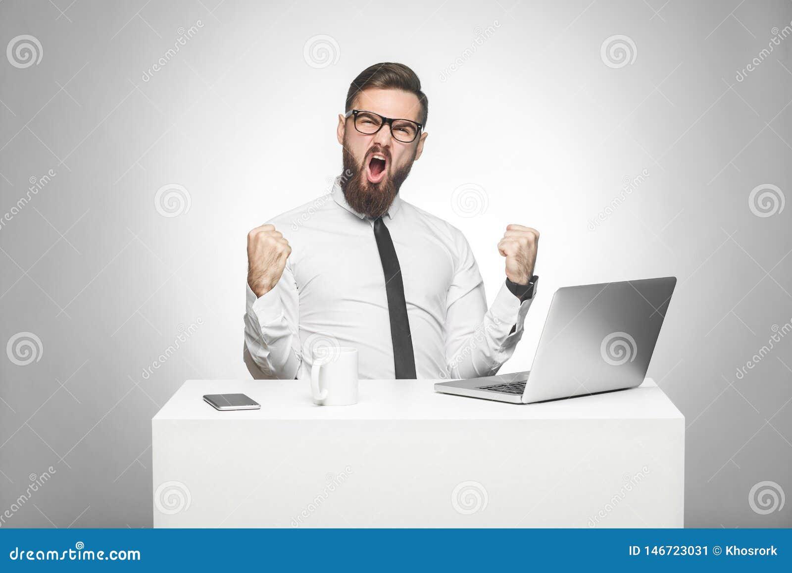 Het portret van knappe verbaasde tevreden positieve gebaarde jonge zakenman in wit overhemd en de avondkleding zitten in bureau e
