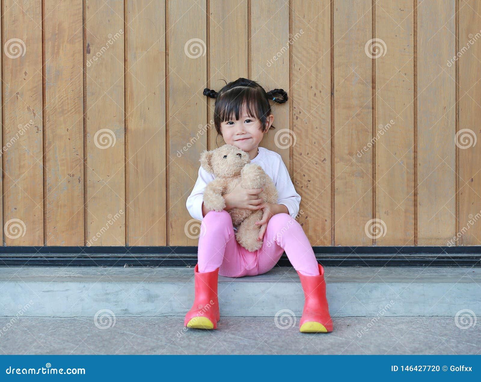 Het portret van leuk meisje zit en koesterend Teddy Bear tegen houten plankmuur