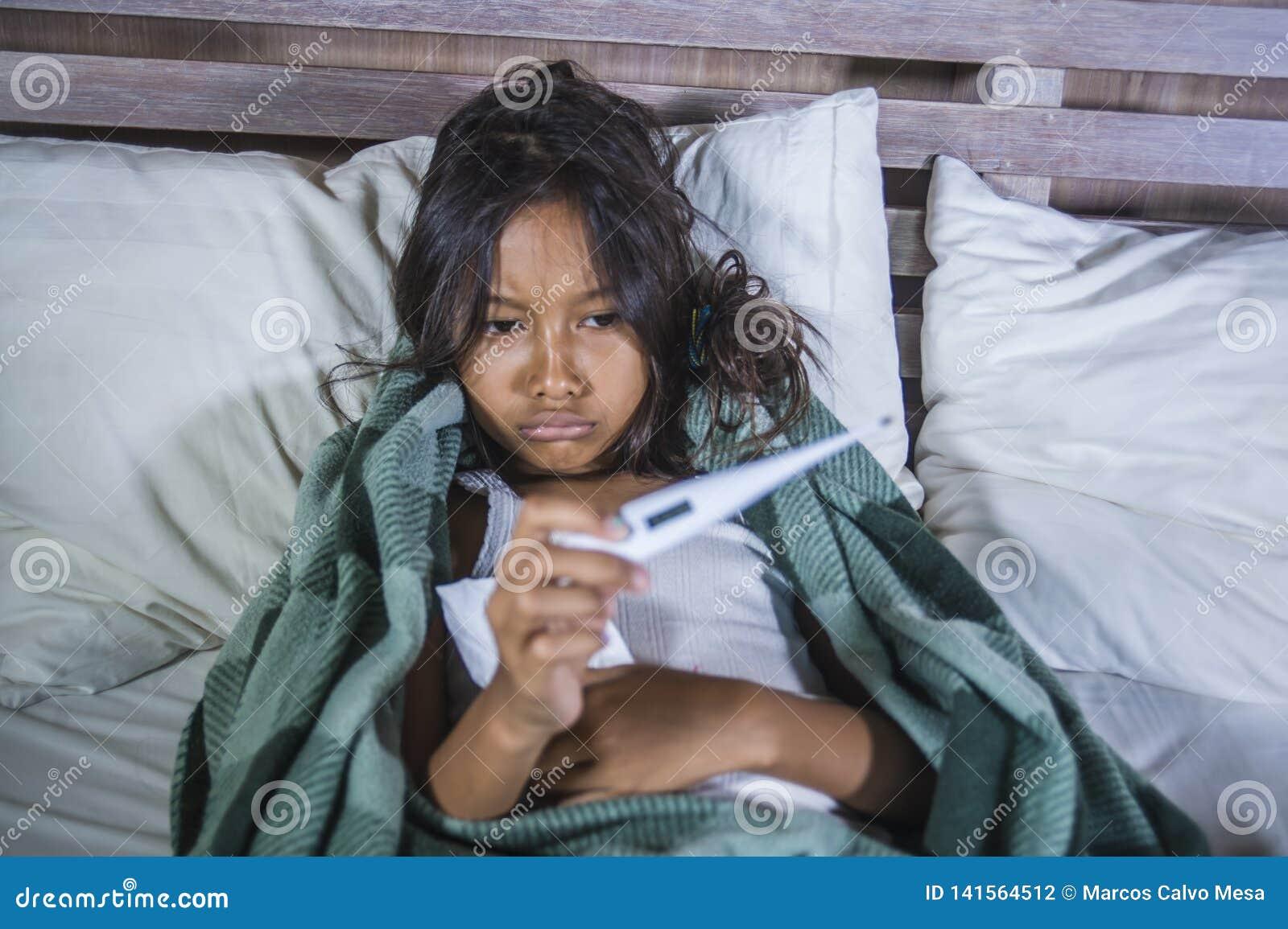 Het portret van het levensstijlhuis van jonge mooie en zoete 8 jaar de oude vrouwelijke van de kindholding thermometer die ziek o