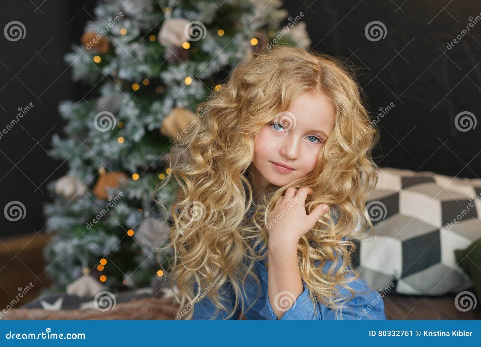 Het portret van mooi blondemeisje zit en raakt haar haar op een bed in Kerstmistijd
