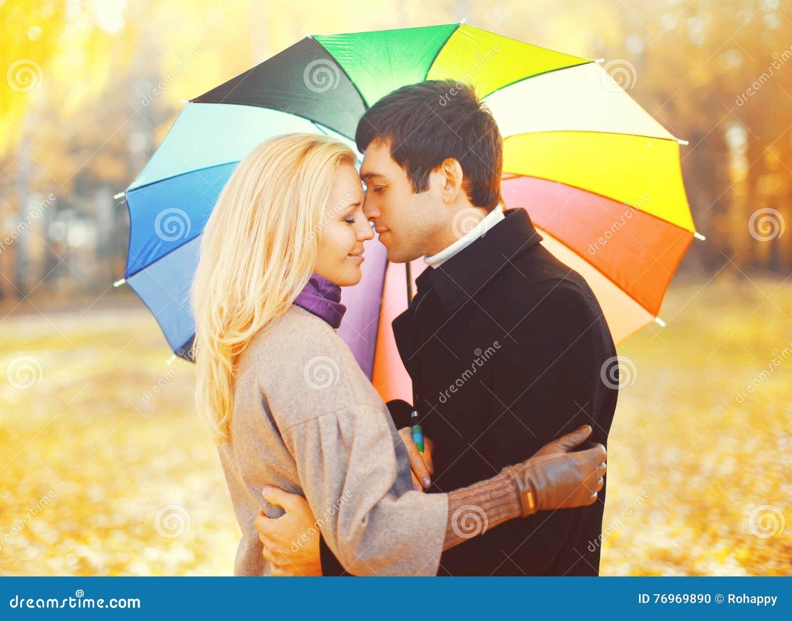 Het portret van romantisch kussend paar in liefde met kleurrijke paraplu samen bij warme zonnige dag over geel doorbladert