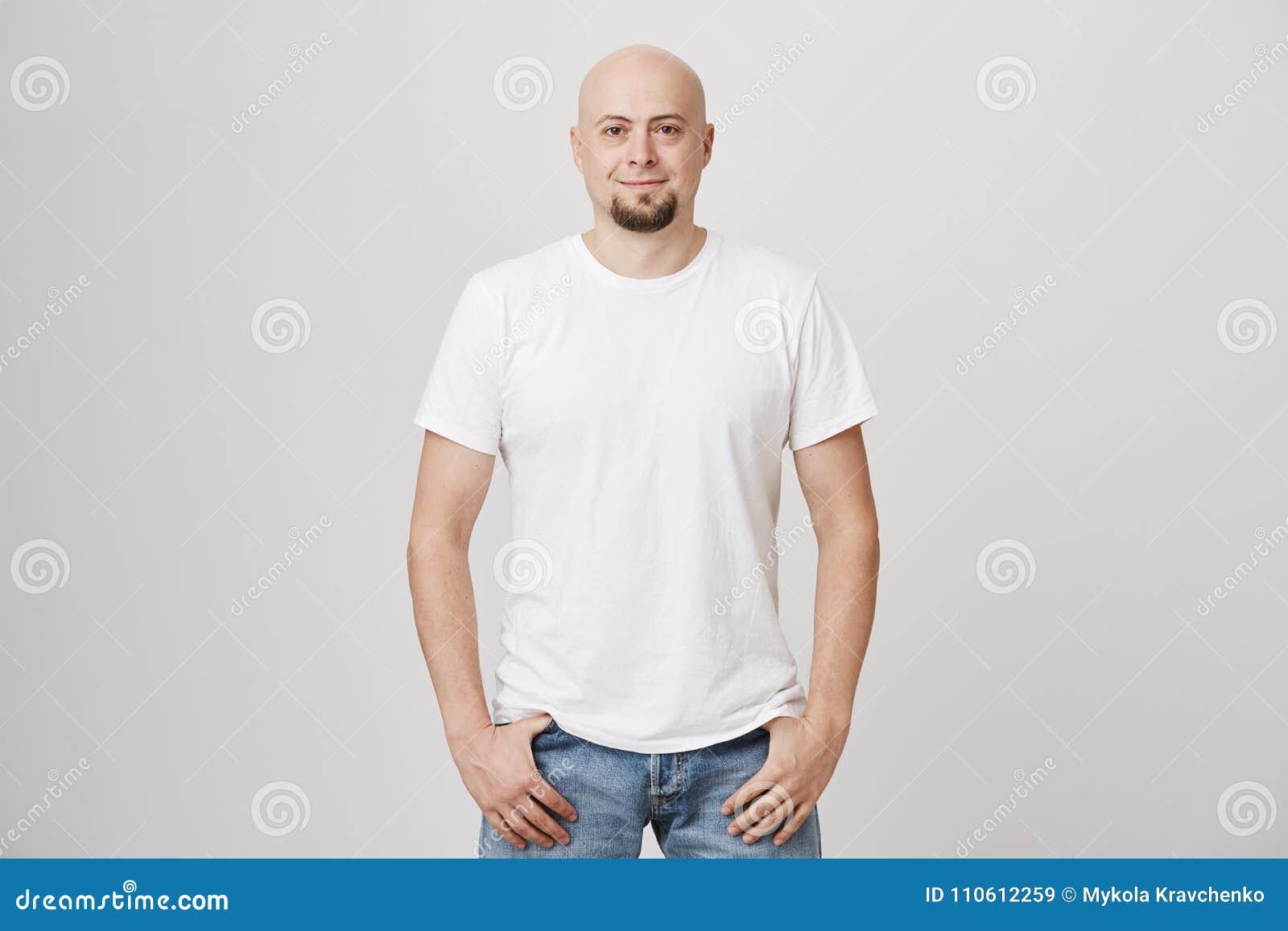 Het portret van zekere knappe kale Kaukasische kerel die toevallige t-shirt dragen en de jeans, het houden dienen zakken in