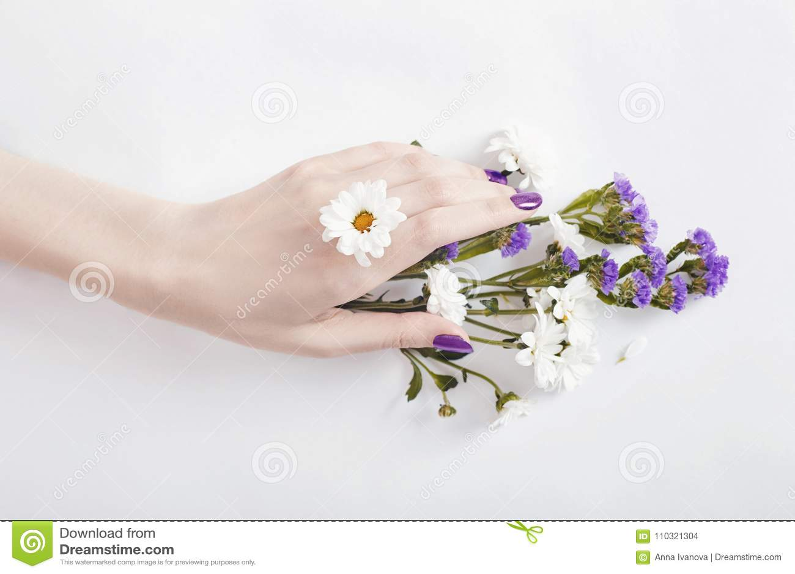 Het portretvrouw van de manierkunst in de zomerkleding en bloemen in haar hand met een heldere het tegenover elkaar stellen make-