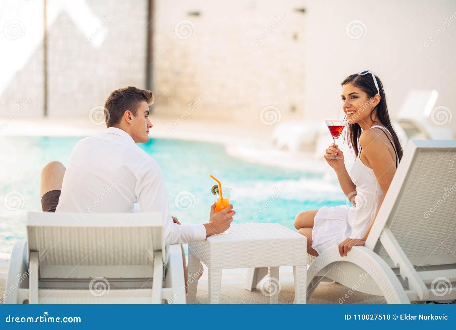 Het positieve gelukkige paar ontspannen door de pool in de vakantietoevlucht van de luxezomer Drinkende cocktails Samen genietend