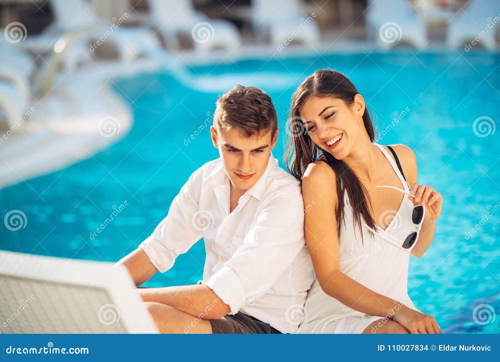 Het positieve gelukkige paar ontspannen door het zwembad in de vakantietoevlucht van de luxezomer Samen genietend van tijd in het