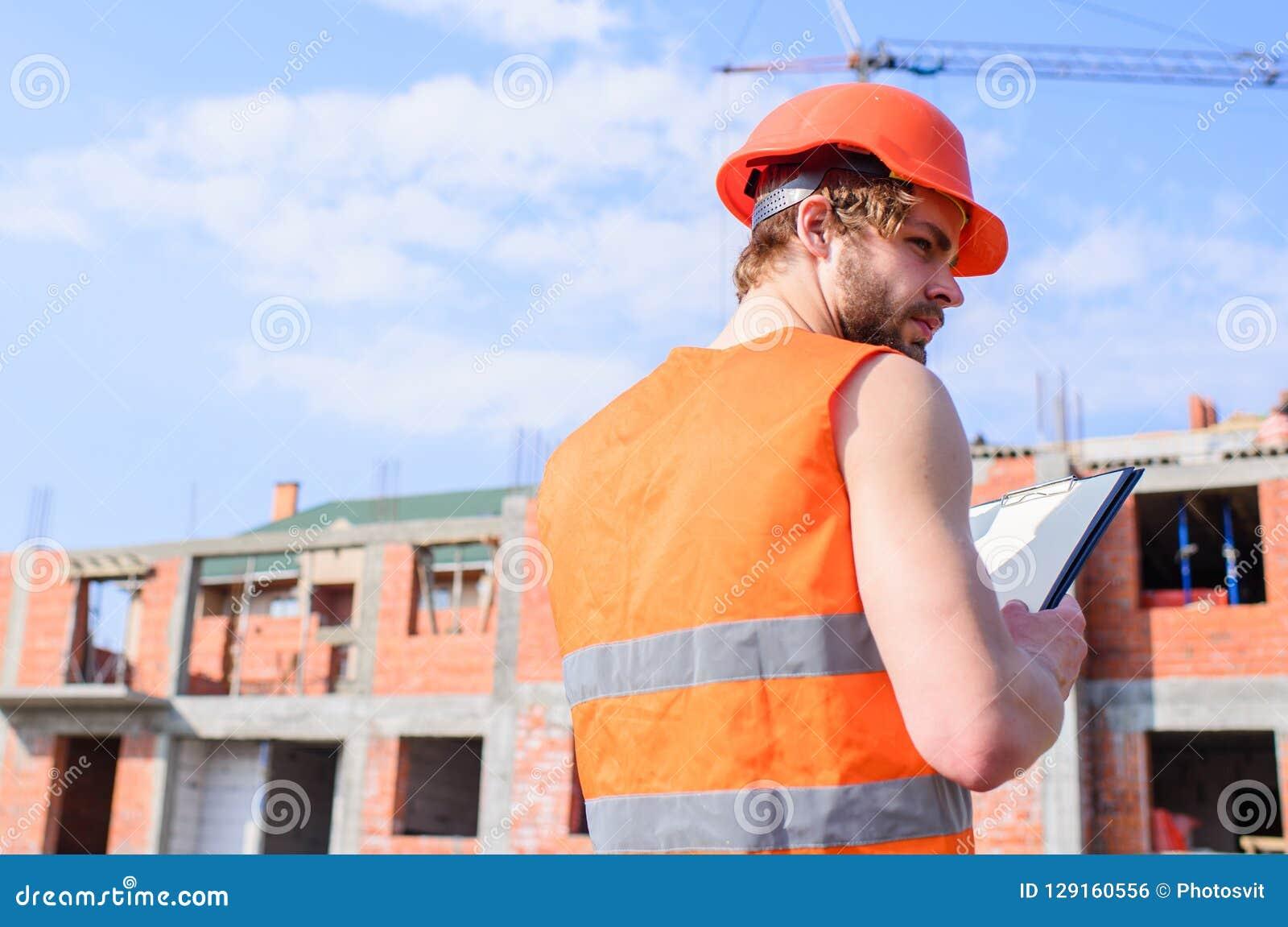 Het proces van de controlebouw Bouwers oranje vest en de helmwerken bij bouwwerf Contractantcontrole volgens