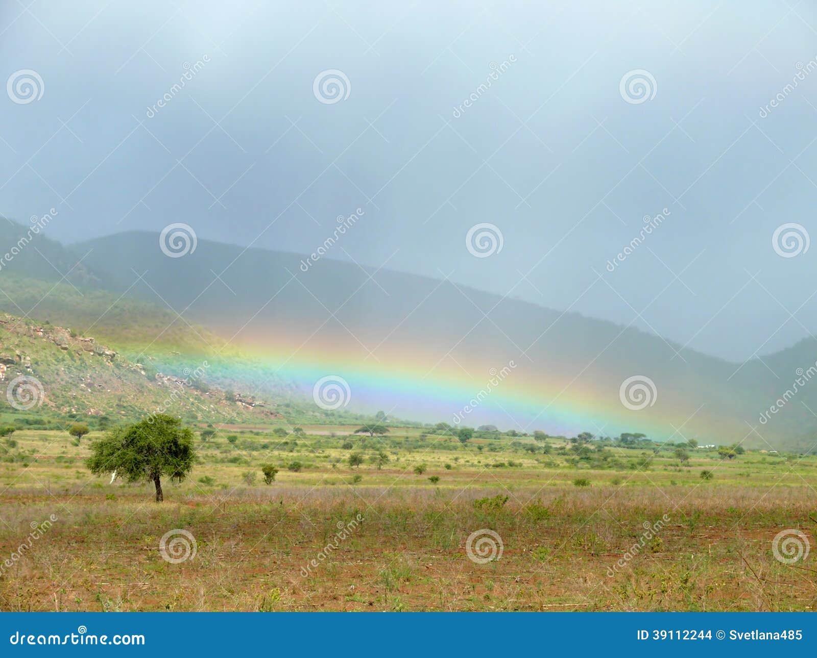 Het regenachtige seizoen. Regenboog aan de grond.