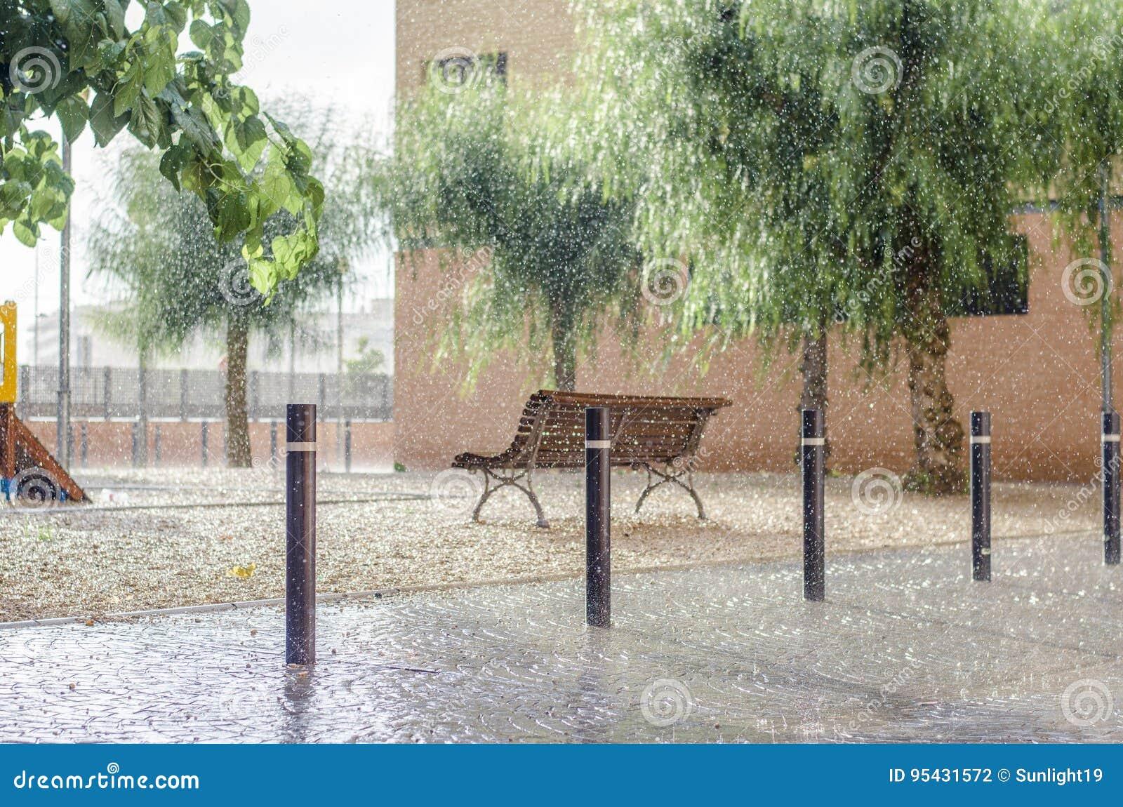 Het regent in een kinderen` s speelplaats, regendalingen het vallen