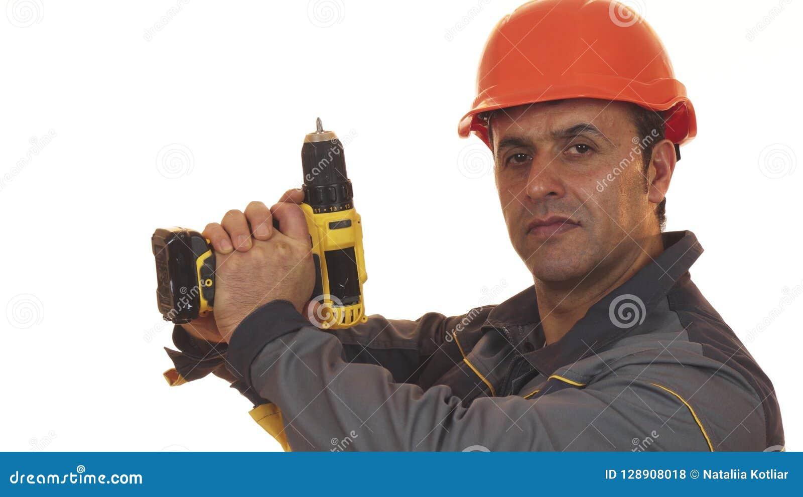 Het rijpe mannelijke construtionarbeider stellen met een boormachine