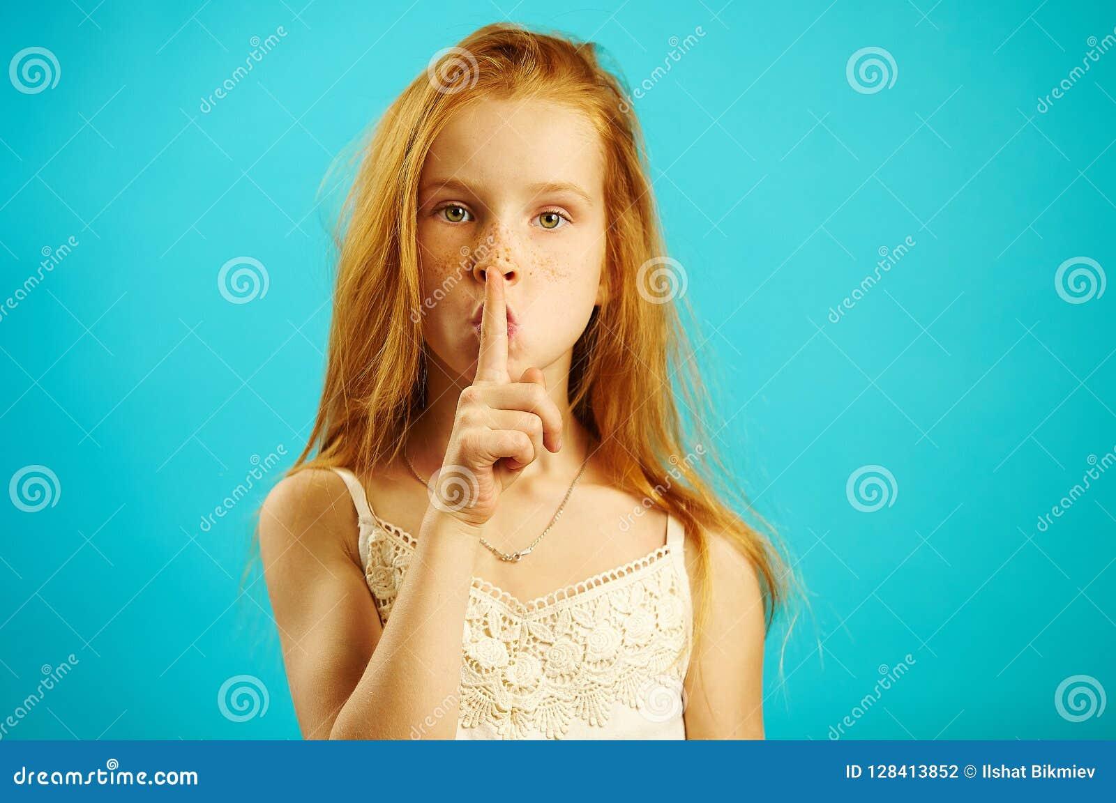 Het rode haired meisje met strikte blik zet haar vinger aan lippen, aantoont geheim en de vertrouwelijkheid, vertelt niet iederee