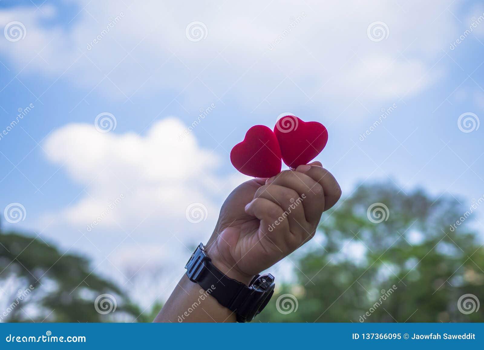 Het rode hart wordt gehouden voor de blauwe hemel en is lichtjes bewolkte en exemplaarruimte de Dag van conceptenvalentine ` s