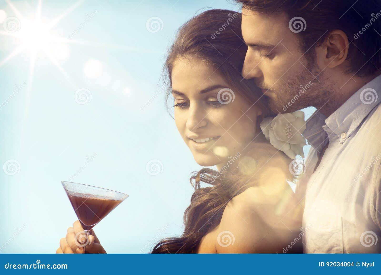 Het romantische paar drinken in zonsondergang