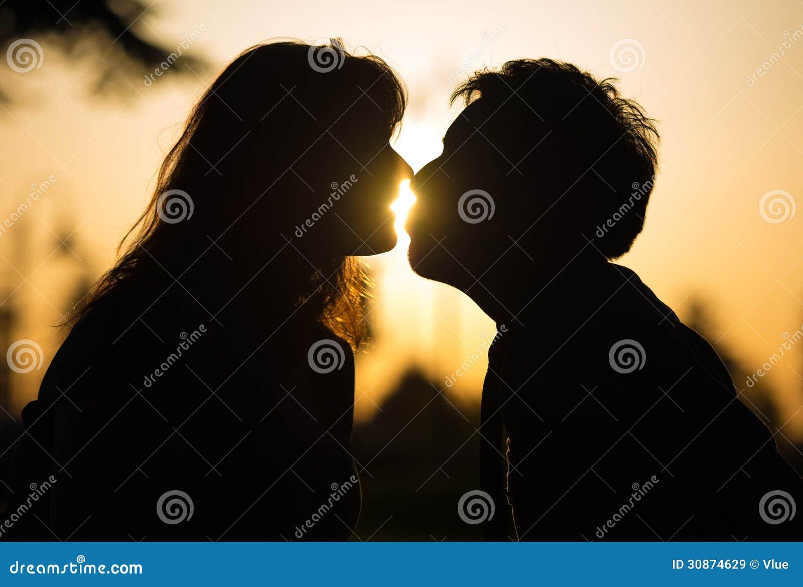 Het romantische paar kussen bij zonsondergang