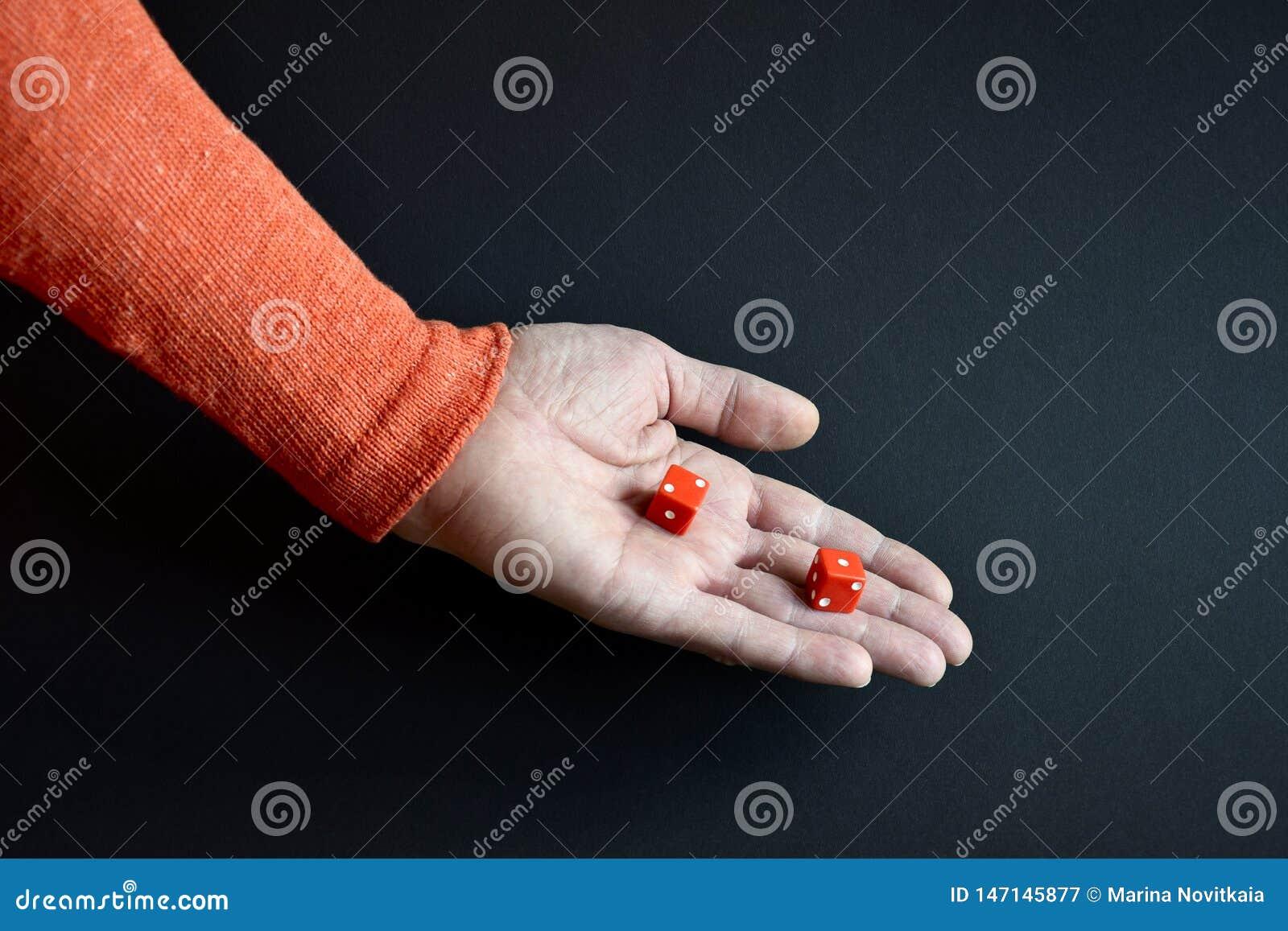 Het rood dobbelt in mannelijke hand neer richtend