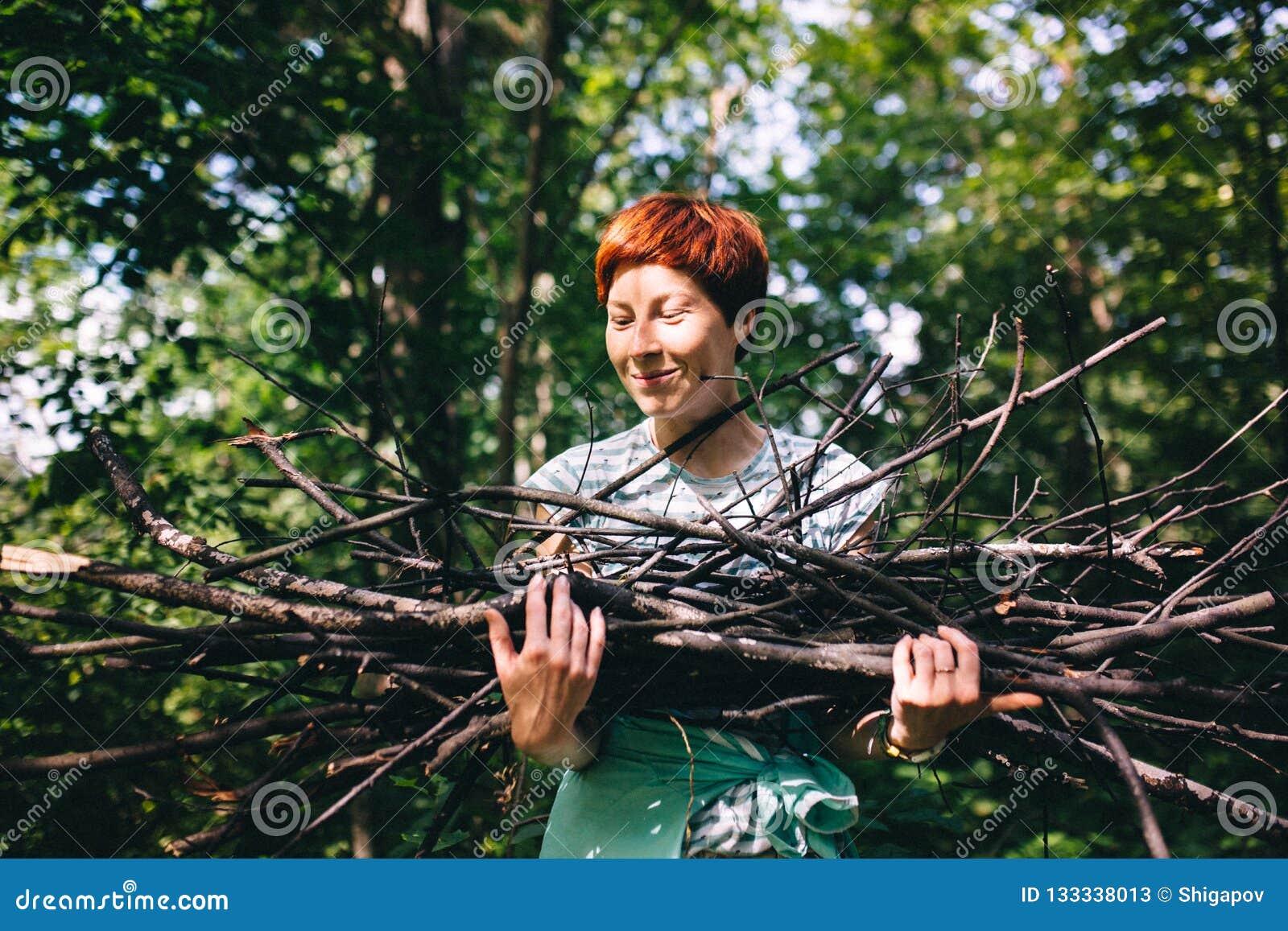 Het roodharige hipstermeisje verzamelt brandhout op de achtergrond van het bos