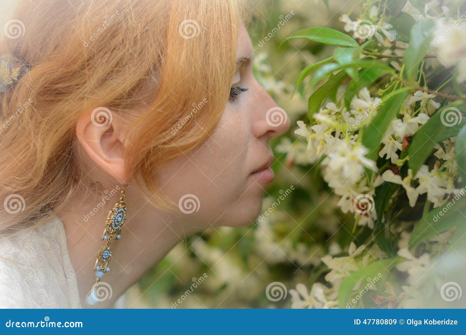 Het roodharige meisje ruikt de witte bloemen