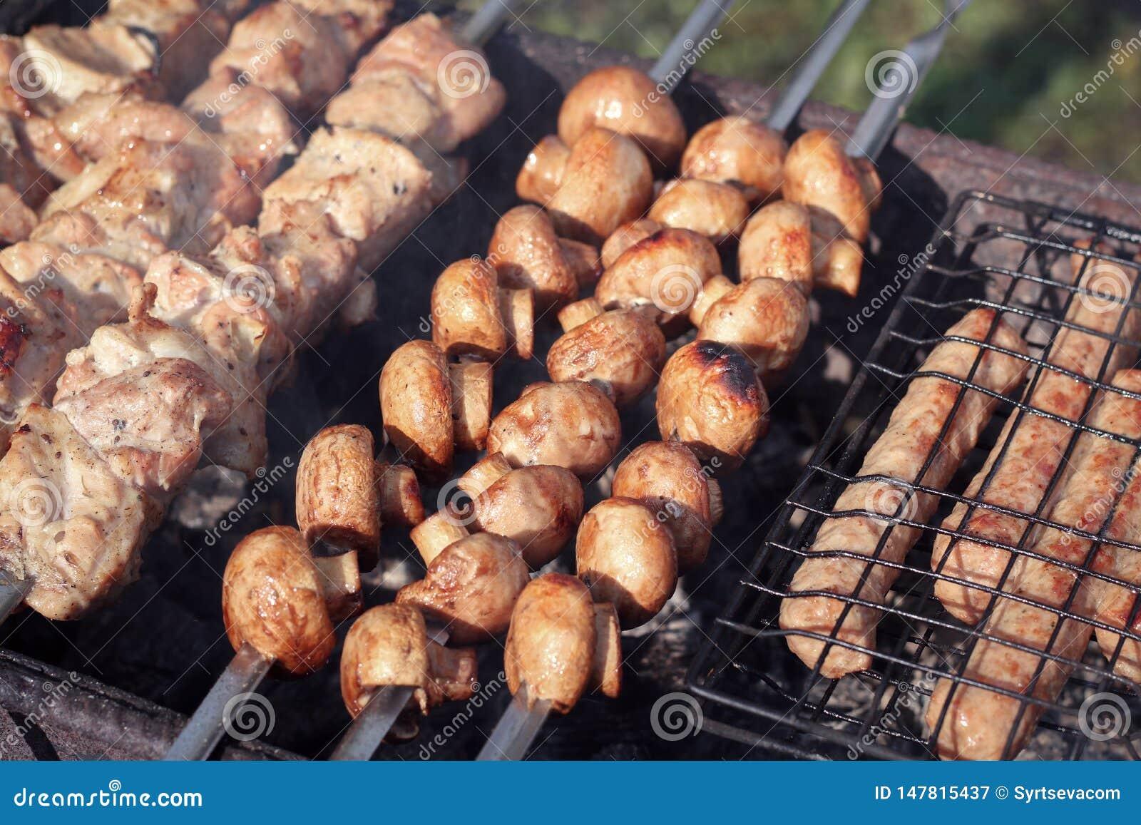 Het sappige geroosterde paddestoelenclose-up op de grill op vleespennen dichtbij sappige stukken van vlees braadde op steenkolen