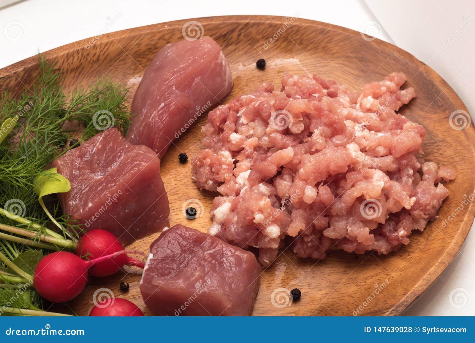 Het sappige vlees hakte in fijngehakt die close-up met brokken ruwe vlees verse groenten, kruiden en kruiden wordt gediend