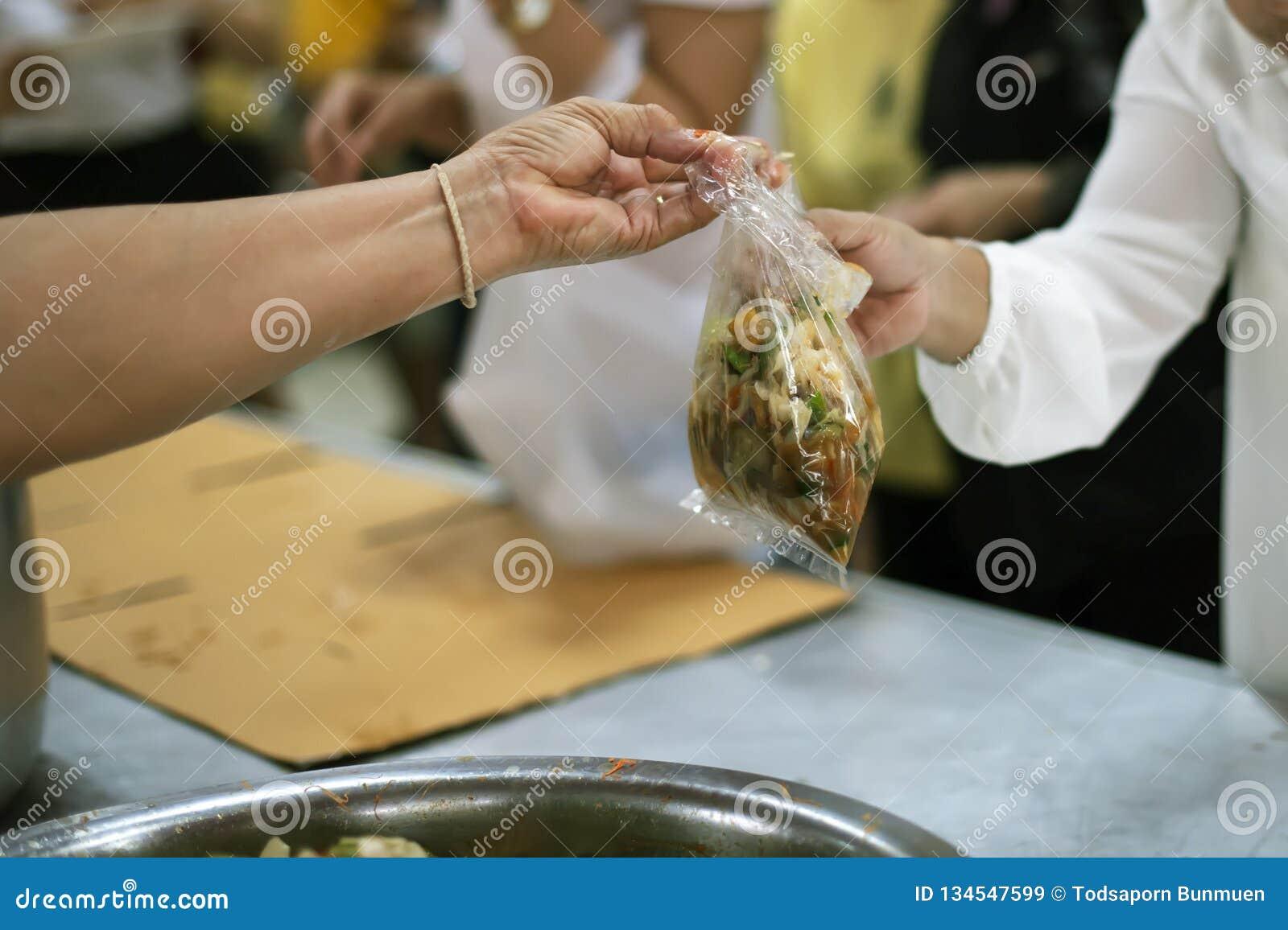 Het schenken van voedsel aan bedelaars om honger te verminderen: het concept het delen van hulp aan mede menselijke wezens in de