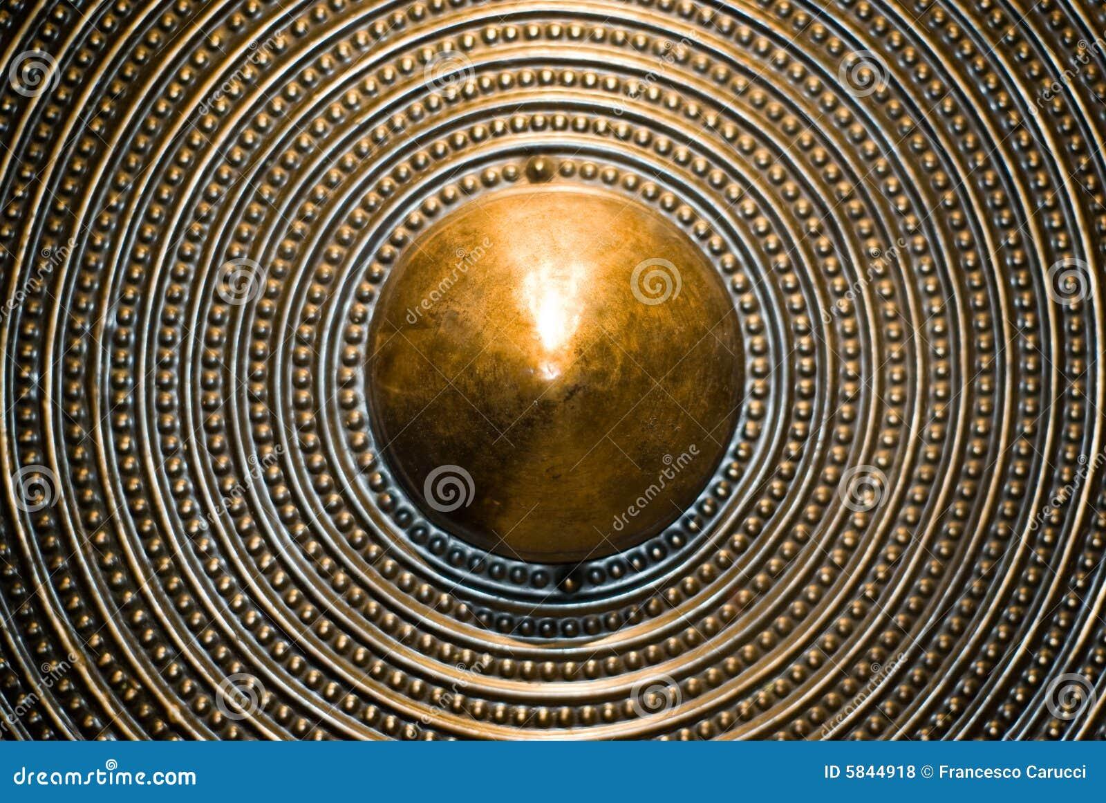 Het schildachtergrond van het brons