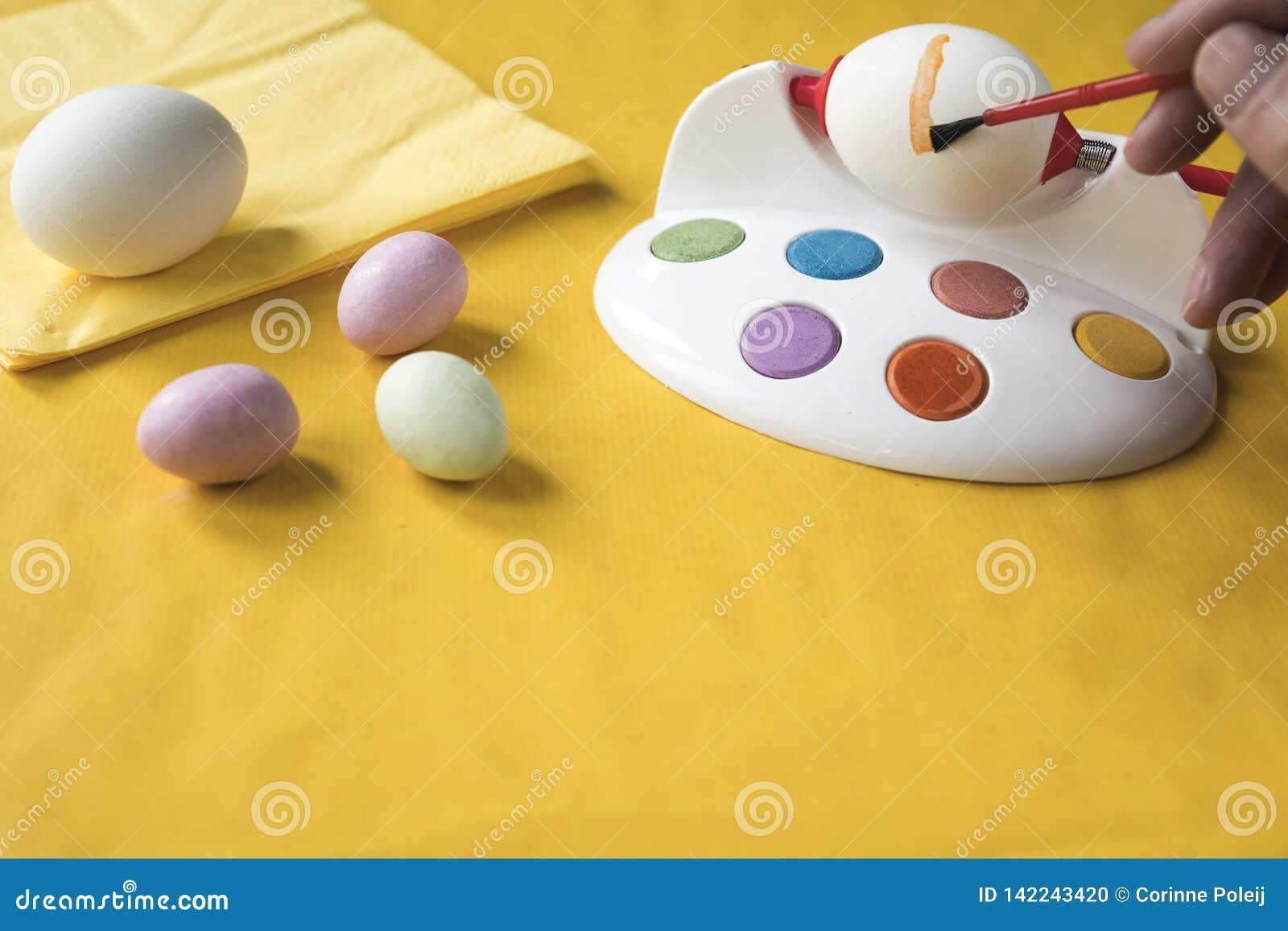 Het schilderen van paaseieren met rode borstel