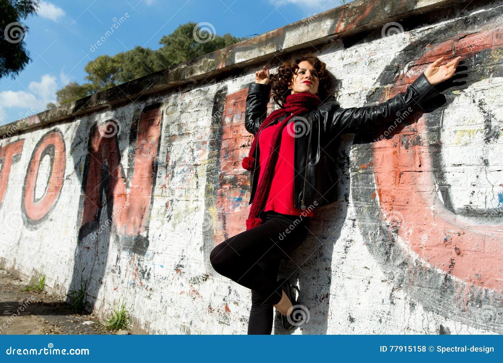 Het schitterende vrouw stellen met graffiti