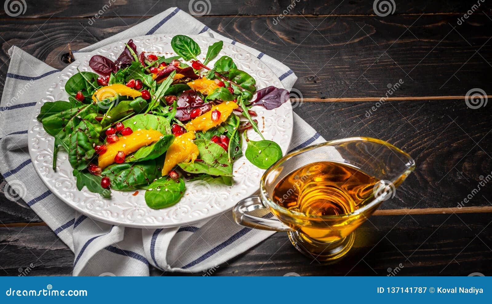 Het schone eten, detox, vegetarisch voedselconcept vegetarische salademango en granaatappel, vitaminesnack op een zwarte houten a