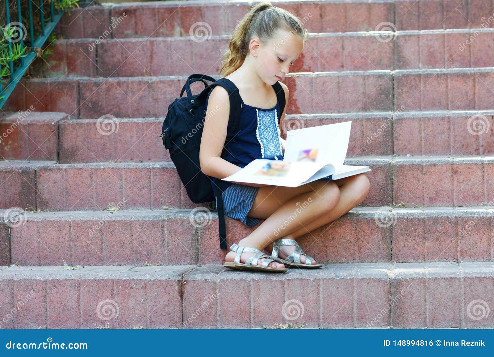 Het schoolmeisje 8 jaar oud het doen thuiswerk op treden leest boek