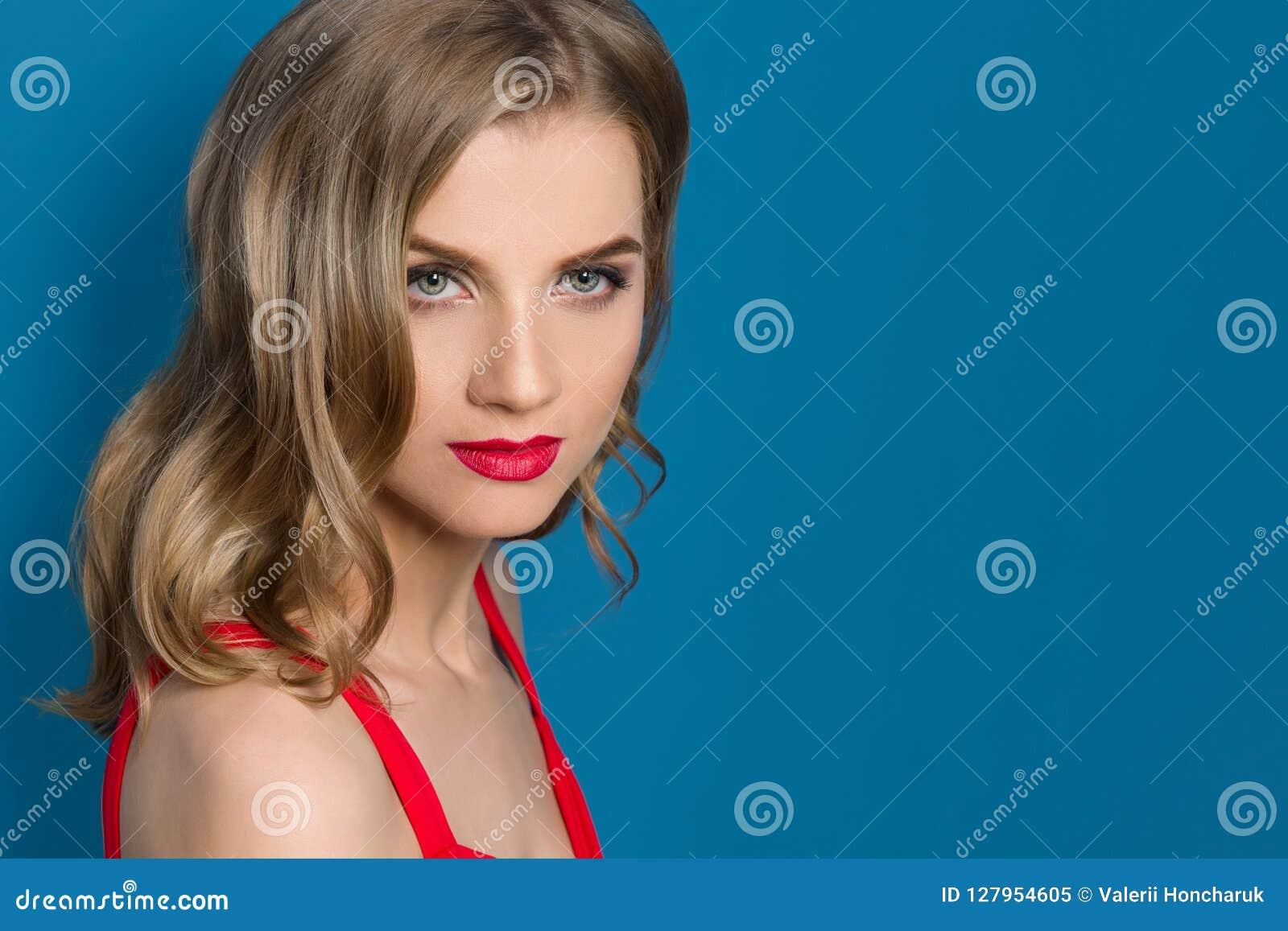 Het schoonheidsportret van jonge blondevrouw met heldere rode lippen, blauwe ogen, in rode kleding op blauwe achtergrond, kopieer