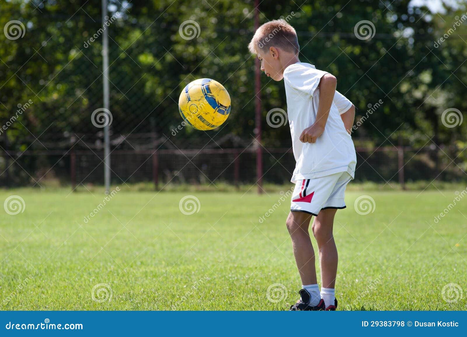 Het schoppen van de jongen voetbal stock foto afbeelding 29383798 - Opslagkast ruimte van de jongen ...