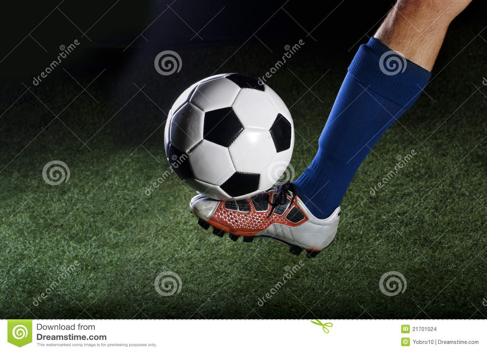 Het schoppen van de voetbalbal op een grasgebied bij nacht
