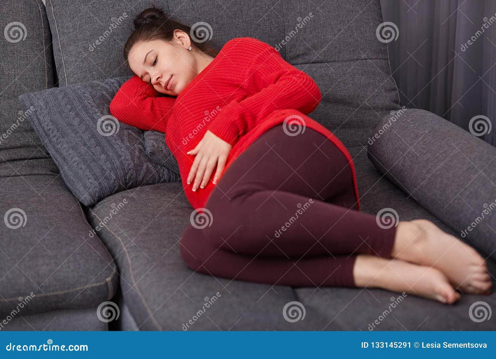 Het schot van rustgevende zwangere vrouw houdt hand op buik, draagt vrijetijdskleding, ligt op comfortabele bank, die dutje, rust