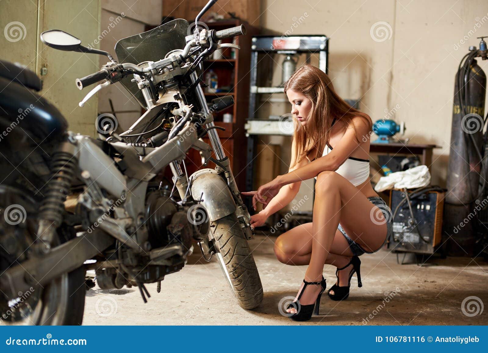 Het schroeien van brunette in korte borrels en high-heeled zit dichtbij motorfiets