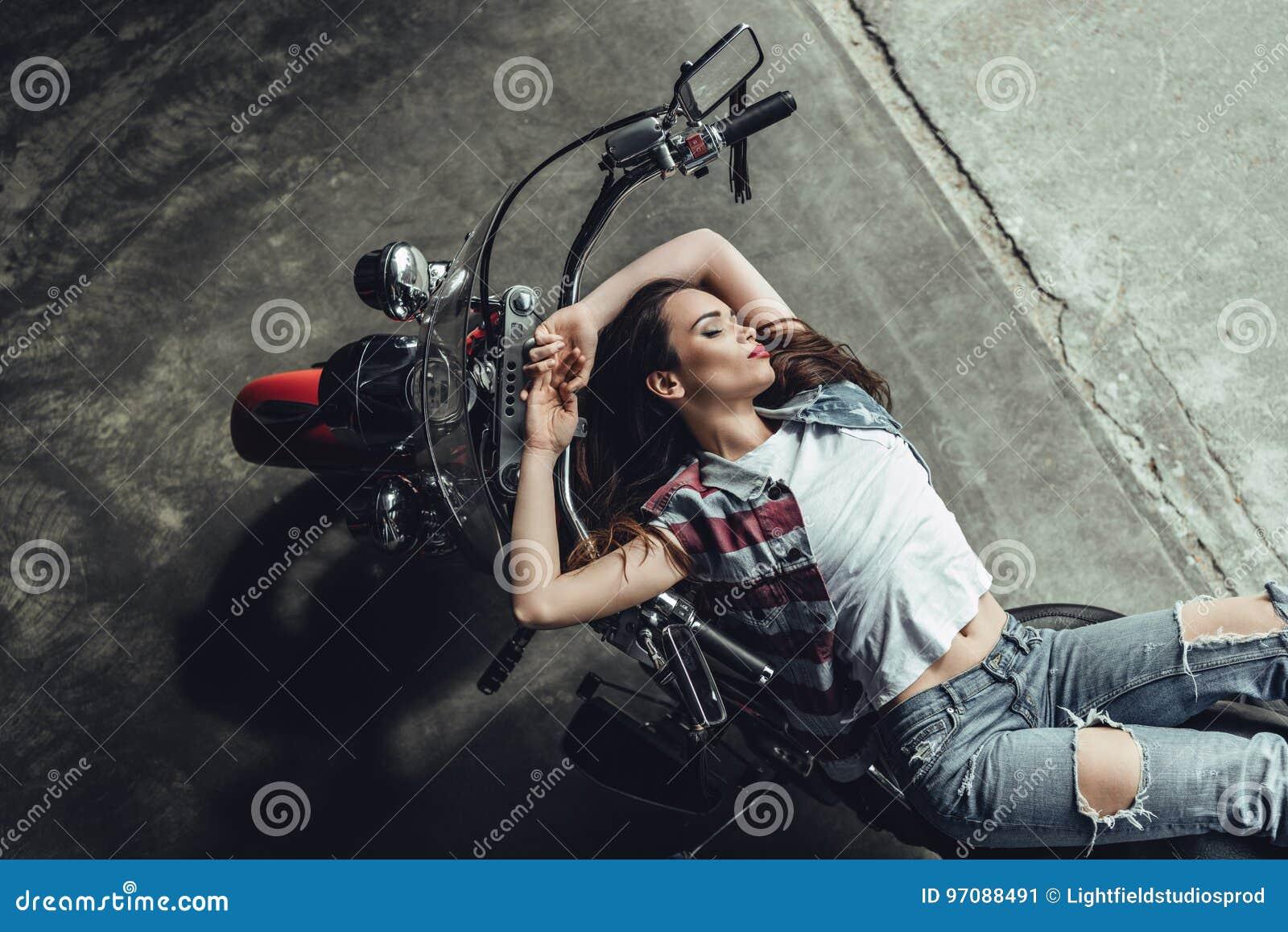 Het sensuele jonge donkerbruine vrouw stellen op motorfiets
