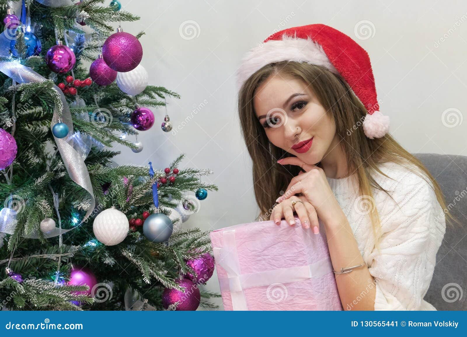 Het sexy blondemeisje in een gebreide sweater en een rood GLB als Santa Claus gelukkig en leuk onderzoekt de camera terwijl het z