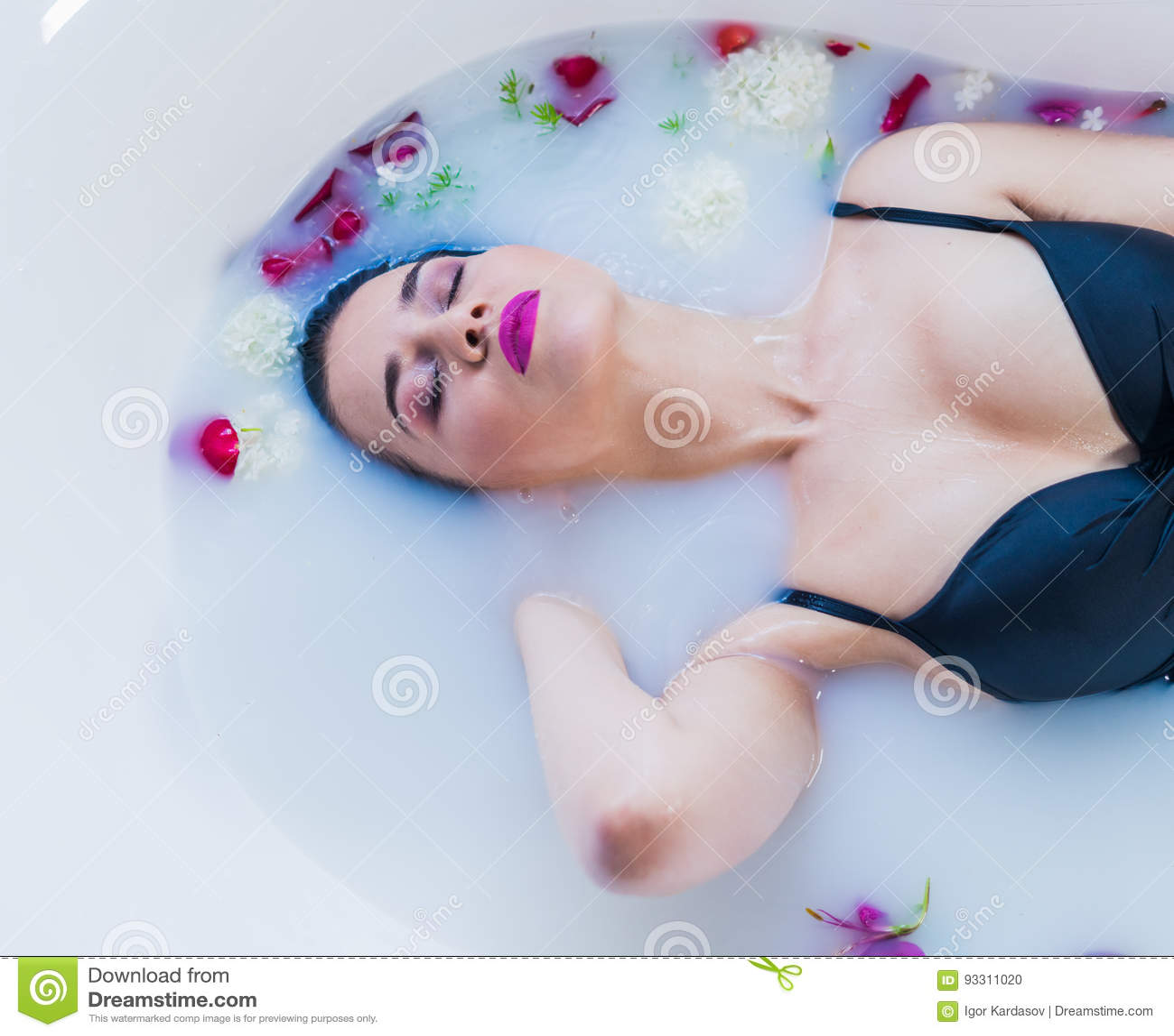 Het sexy donkerbruine vrouw ontspannen in heet melkbad met bloemen