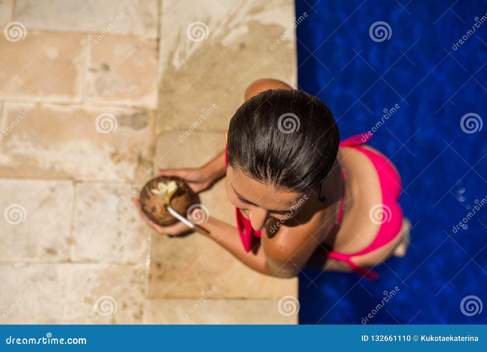 Het sexy slanke donkerbruine jonge vrouwelijke stellen met verse kokosnoot in pool met kristal blauw water De koninklijke tropisc