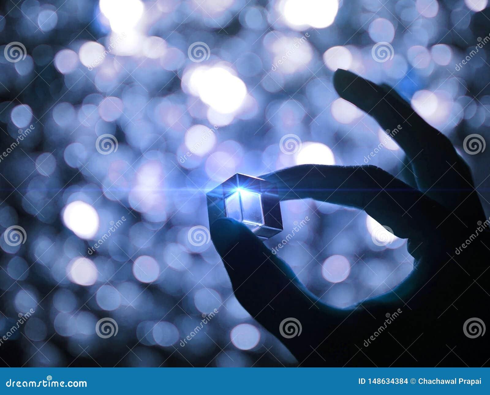 Het silhouet van een mannelijke hand die een glaskubus met blauwe technologieverlichting houden verlichtte uitgevoerd en bokeh ac