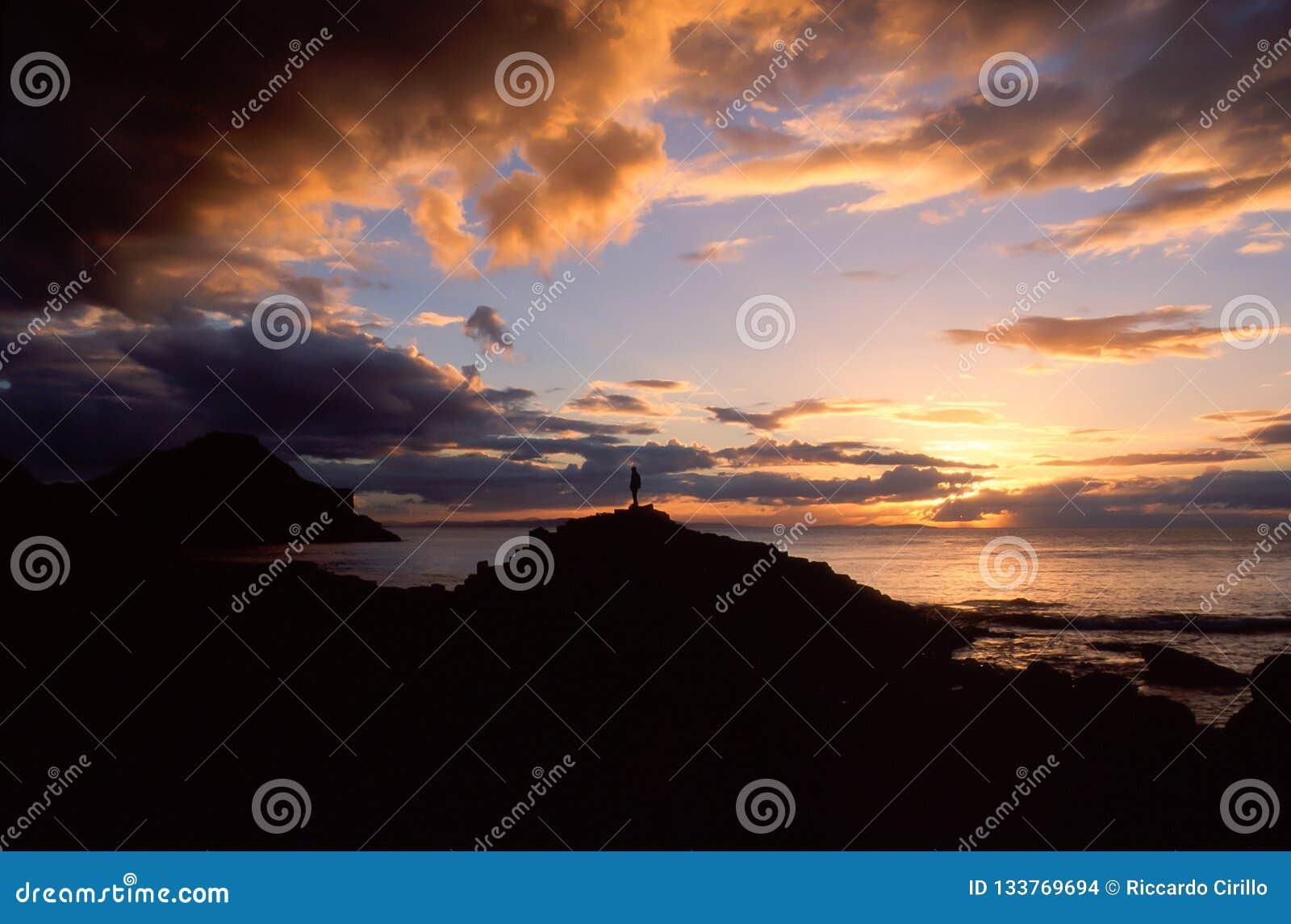 Het silhouet van een mens in het natuurlijke landschap van een zonsondergang over