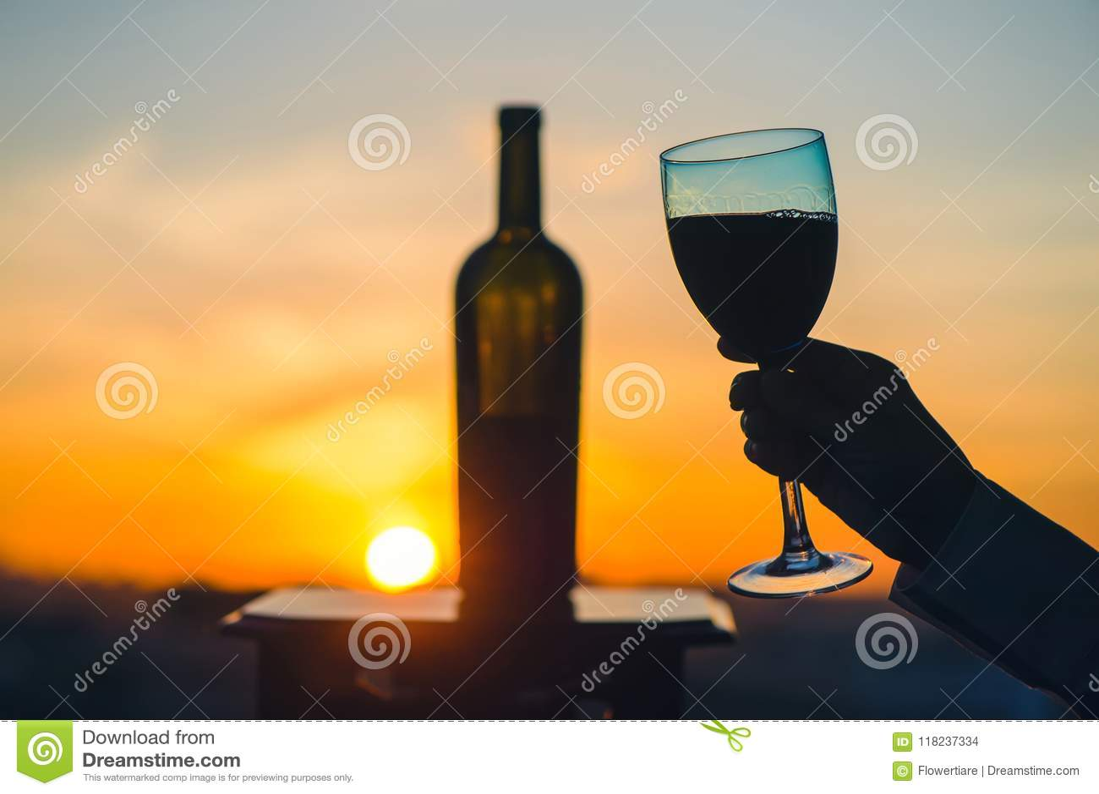 Het silhouet van mannetje en wijfje overhandigt roosterende wijn op zonsondergangachtergrond Het romantische paar vieren bij een
