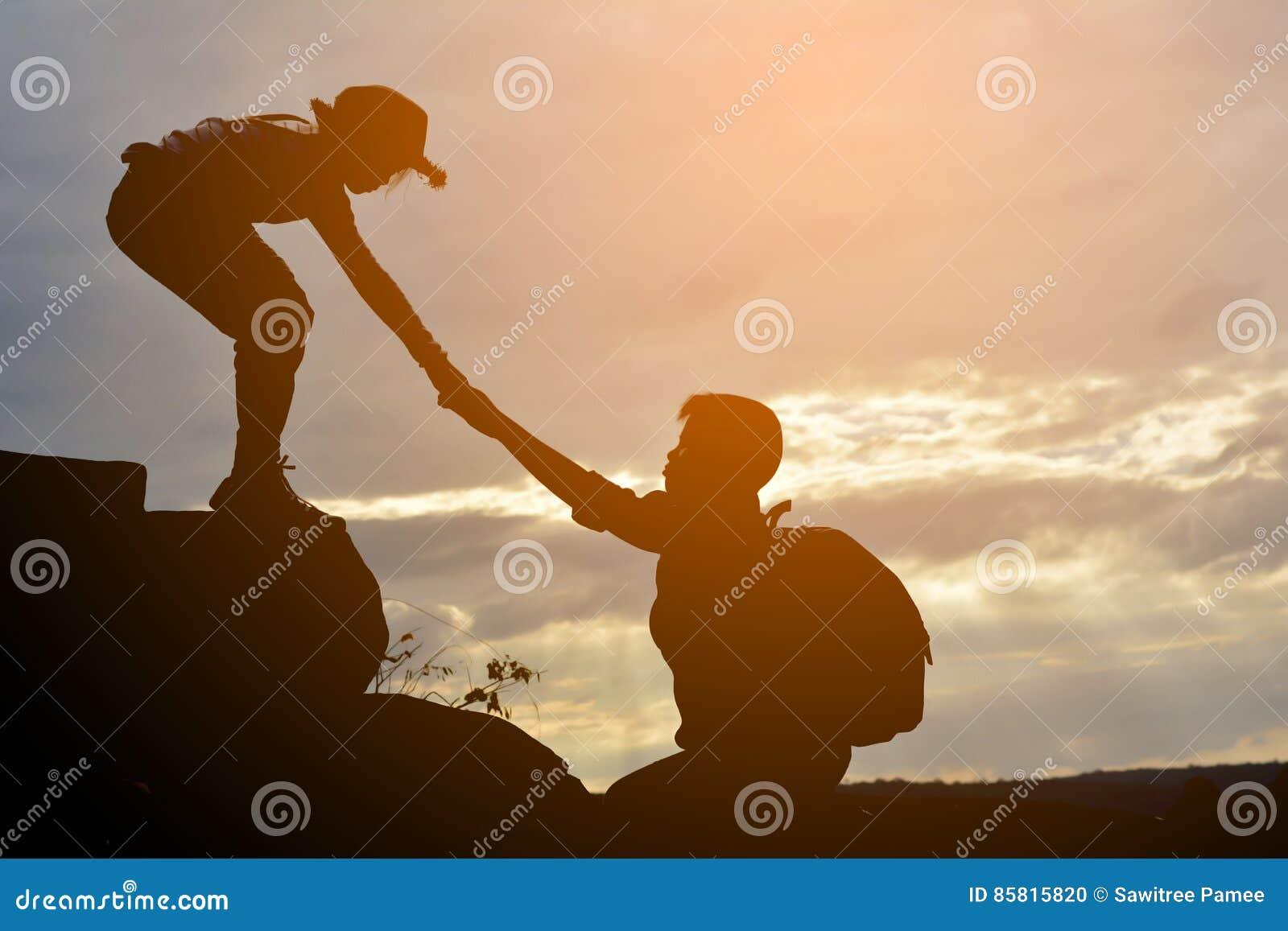 Het silhouet van meisje helpt een jongen op berg